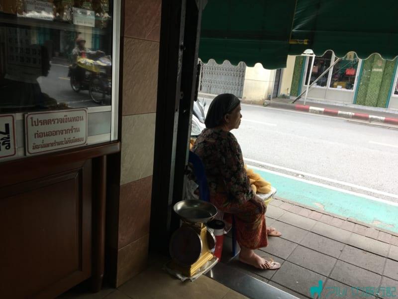 マンゴー店の店先に座っているおばあちゃん
